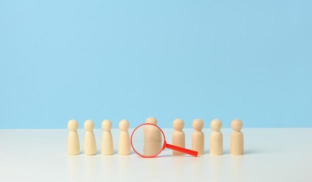 Holzfiguren von männern und eine rote lupe auf blauem grund. recruiting für das unternehmen, gleichgesinnte und teamwork. suche nach talenten