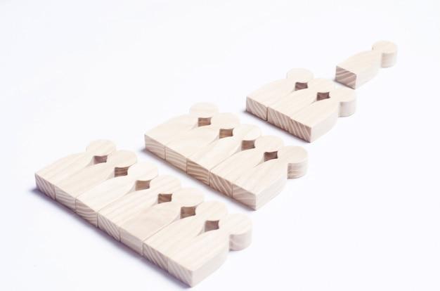 Holzfiguren von menschen auf einem weißen hintergrund in form einer pyramide der sozialen hierarchie