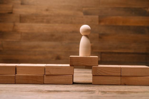 Holzfiguren von menschen stehen auf brückenbrettern als konzept von risiken in geschäft und strategie