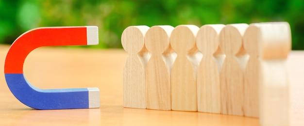 Holzfiguren von menschen und ein magnet.