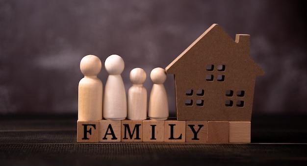 Holzfigurenfamilie, die neben einem holzhaus auf einem holzwürfel steht, der das wort familie schreibt.