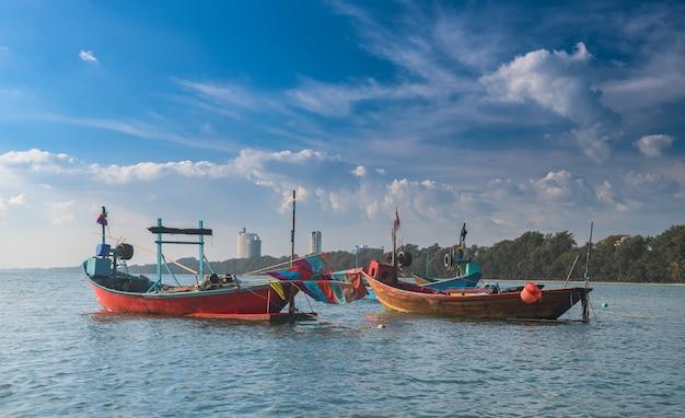 Holzfischereiboot im meer mit sonnenlicht im freien und bewölktem himmel