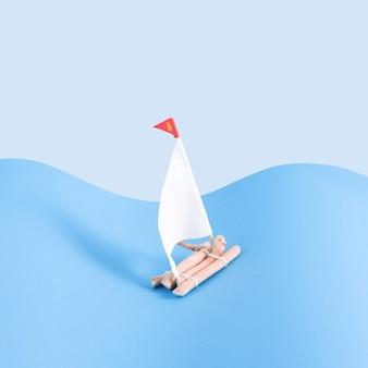 Holzfloß mit segeln auf hell- und dunkelblauem hintergrund. minimales konzept. quadrat mit kopienraum