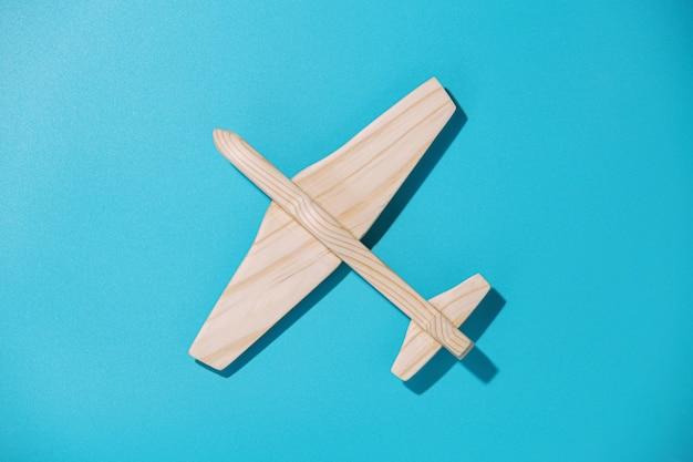 Holzflugzeug auf blauem hintergrund, draufsicht