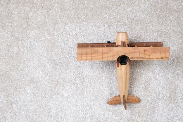 Holzflugzeug auf einem weißen teppich.