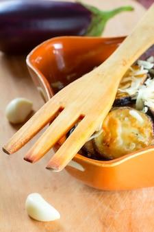 Holzgabel, gebratene auberginen mit knoblauch in einer keramikschale und rohe knoblauchzehen und auberginen