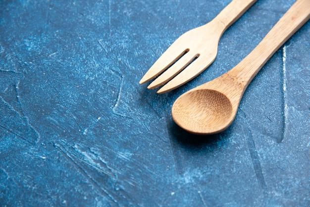 Holzgabellöffel von unten auf freiem platz der blauen oberfläche
