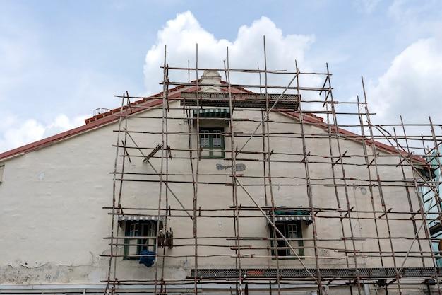 Holzgerüst am haus, renovierung. gerüst an gebäude, wand und fenster. gerüstsystem im bau, singapur. baustelle, strukturdetail im bau