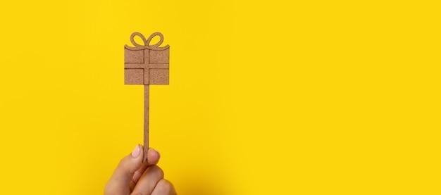 Holzgeschenk in der hand über gelbem hintergrund