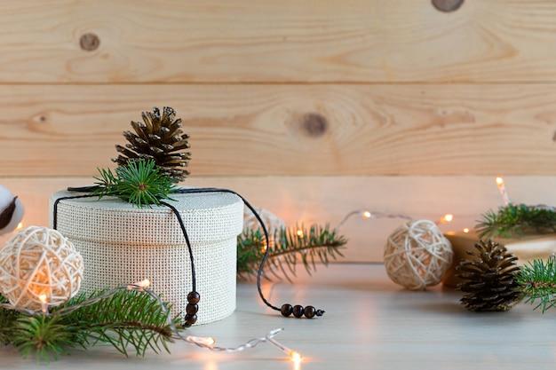 Holzgeschenk in öko-verpackung mit fichtenzweig, tannenzapfen. null abfall weihnachten.