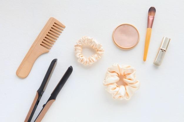 Holzhaarbürste haarglätter und gelber seidenhaarbürste und puder auf weißer flacher lage