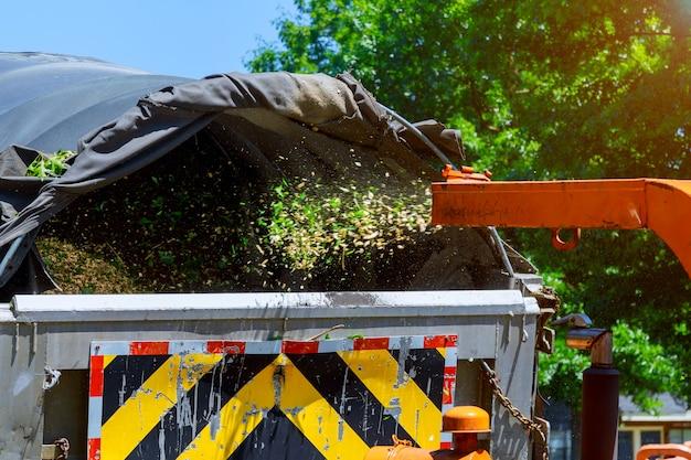 Holzhacker, der einen tragbaren maschinenbaum in einen lkw zerreißt