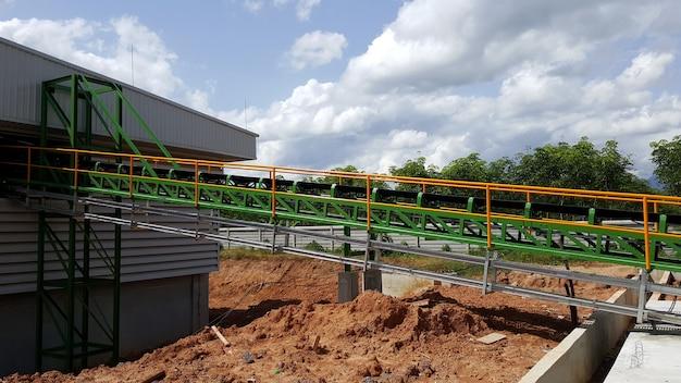 Holzhacker verarbeiten holzhackschnitzeltransport per förderband zum holzhackschnitzel-brennstofflager