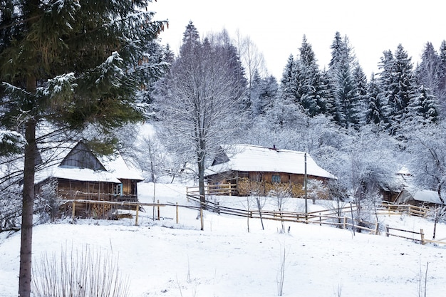 Holzhäuser im schneebedeckten wald