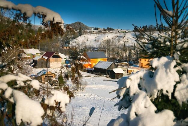 Holzhäuser in einem dorf in der schneewinternacht unter blauem dunklem himmel mit sternen