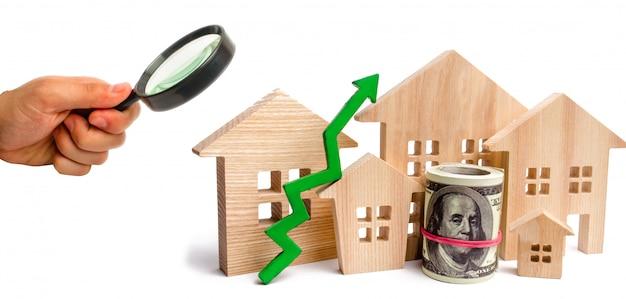 Holzhäuser mit einem grünen pfeil nach oben. konzept der hohen nachfrage nach immobilien.