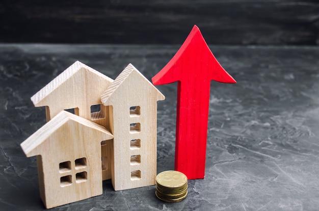Holzhäuser mit einem roten pfeil nach oben. konzept der hohen nachfrage nach immobilien.