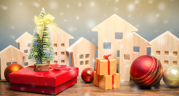 Holzhäuser, weihnachtsbaum und geschenke.