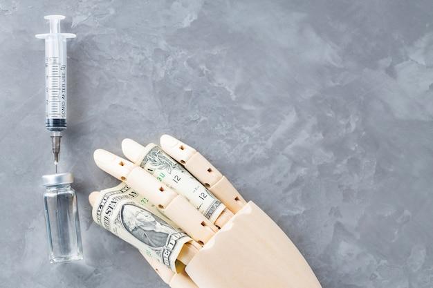 Holzhand mit fläschchen mit spritzenimpfstoff und einem dollar auf grauem hintergrund