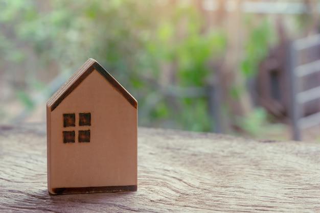 Holzhaus auf holztisch. immobilieninvestition und haushypothek-finanzkonzept. platz kopieren