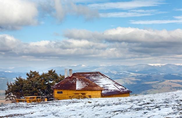 Holzhaus auf karpaten-bergplateau im oktober mit erstem winterschnee