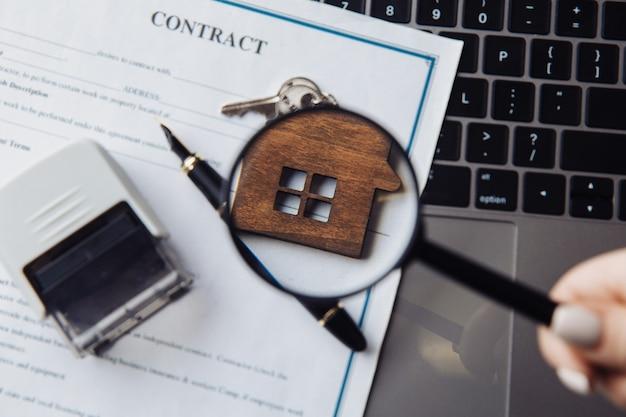 Holzhaus, lupe und vertrag auf einem laptop. konzept der miete, suche oder hypothek. nahansicht.