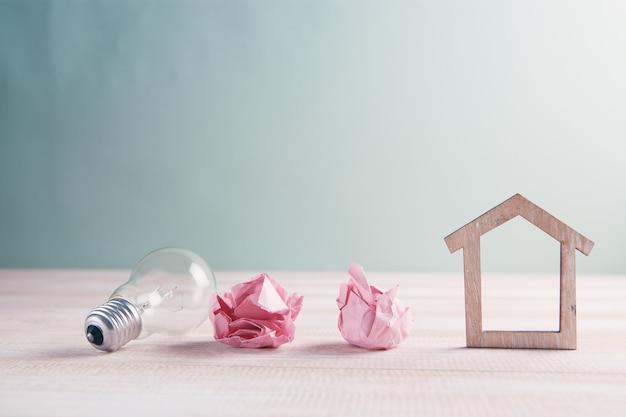 Holzhaus mit glühbirne auf dem tisch, ein symbol für den bau, kreative glühbirnenidee