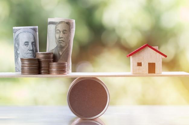 Holzhaus, münzengeld, us-dollar, jpy auf hölzerner runder kastenbalance für das träumen von häusern