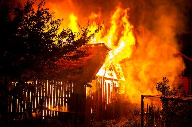 Holzhaus oder scheune, die auf feuer nachts brennen.