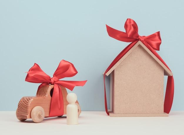 Holzhaus und auto mit miniatur-holzfigur eines mannes, hypotheken- und darlehenskonzept, nahaufnahme