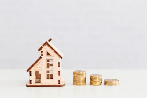 Holzhaus und münzen stapel