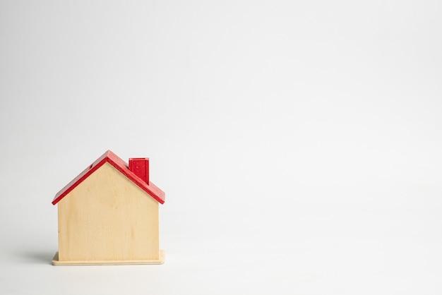 Holzhaus und spielzeugmodell lokalisiert auf weißem hintergrund. konzept hauskäufer oder hausverkäufer