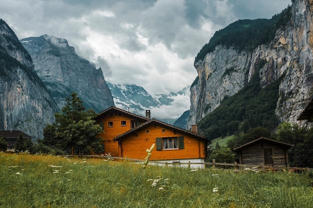 Holzhauschalet mit fensterläden in lauterbrunnental schweiz wiesen und dorf in swiss