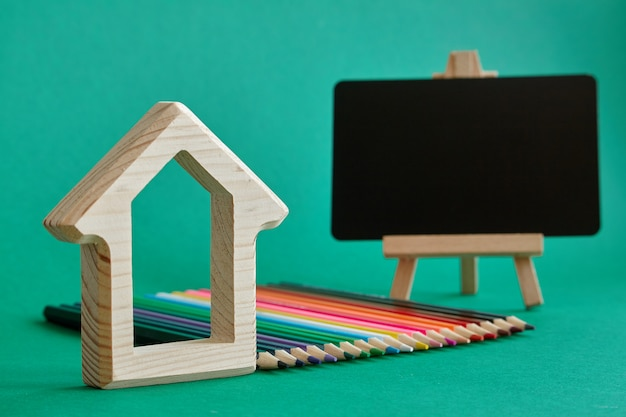 Holzhausfigürchen, miniaturkreidebrett auf einem gestell und farbbleistifte, die durch regenbogenfarben ausgebreitet werden, lokalisieren auf grünem hintergrund, zurück zu schule, selektiver fokus
