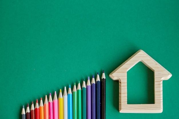 Holzhausfigürchen- und -farbbleistifte, die durch regenbogenfarben ausgebreitet werden, lokalisieren auf grünem hintergrund, zurück zu schule, selektiver fokus