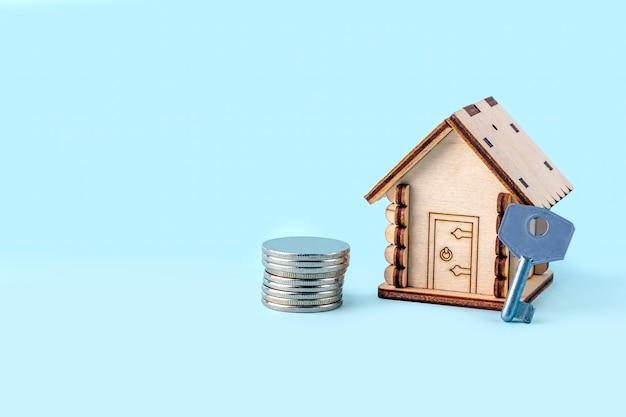 Holzhausmodell, aktiengeld und schlüssel auf blauem hintergrund. konzept des kaufs und verkaufs von häusern und immobilien. hausratversicherung, eigentum und hypothek. kopieren sie platz für text