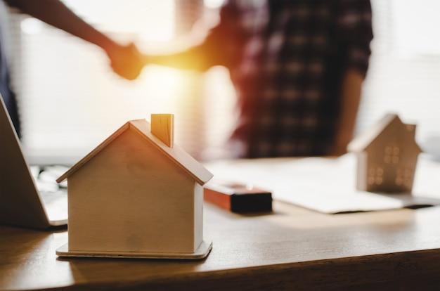 Holzhausmodell auf arbeitsplatzschreibtisch mit den bauarbeiterteamhänden, die gruß rütteln, beginnen oben neuen projektvertrag des plans