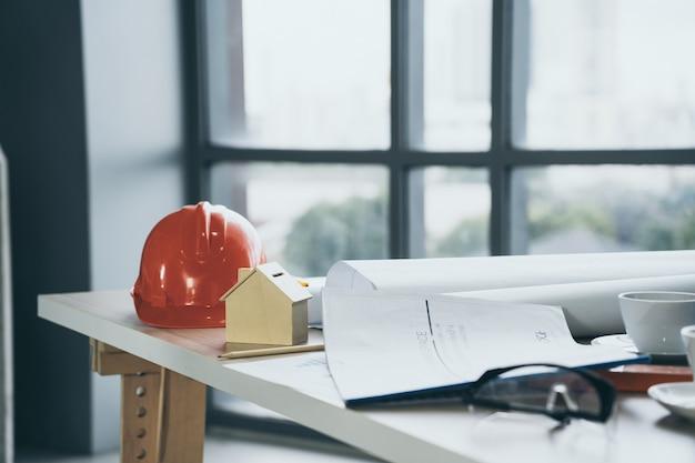 Holzhausmodell auf dem schreibtisch im baustellenbüro