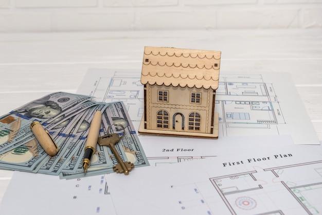 Holzhausmodell mit echtem schlüssel auf blaupause