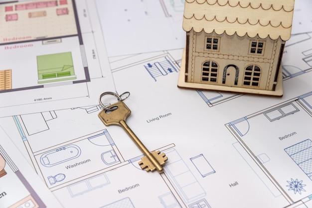 Holzhausmodell mit schlüssel auf hausplan
