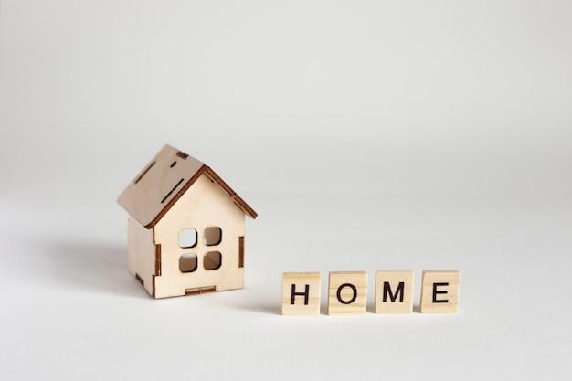 Holzhausmodell und holzbuchstaben mit der aufschrift home