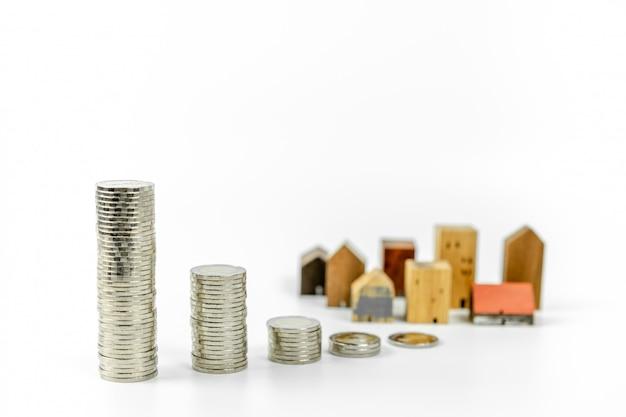 Holzhausmodell und reihe des münzengeldes auf weißem hintergrund