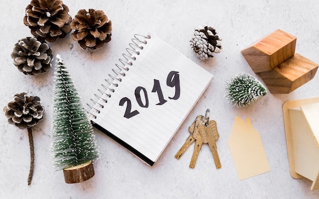 Holzhausmodell; weihnachtsbaum; kiefernzapfen; schlüssel und 2019 auf spiralblock gegen konkrete kulisse geschrieben
