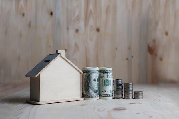 Holzhaussparschwein mit dollargeld und -münze auf holztisch über einsparungsgeld der hölzernen metapher für kaufhaus und immobilien