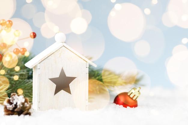 Holzhausweihnachten mit dekorationen auf weißem schneehintergrund mit goldenen lichtern