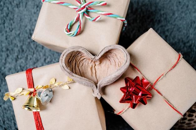 Holzherz auf weihnachtsgeschenken mit glocken und bändern