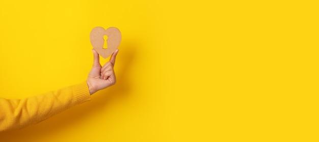 Holzherz mit schlüsselloch in der hand über gelbem hintergrund