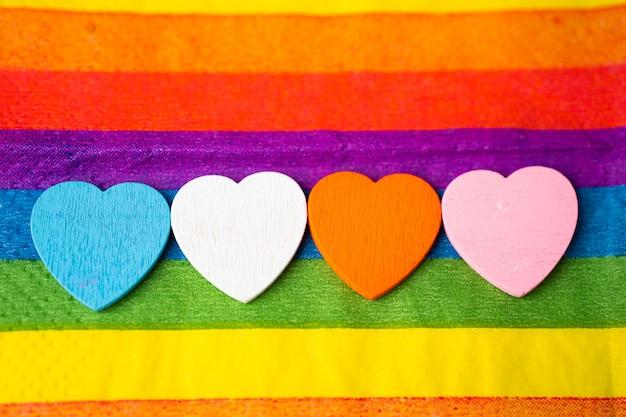 Holzherzen auf buntem regenbogenstoff, symbol des lgbt-stolzmonats.