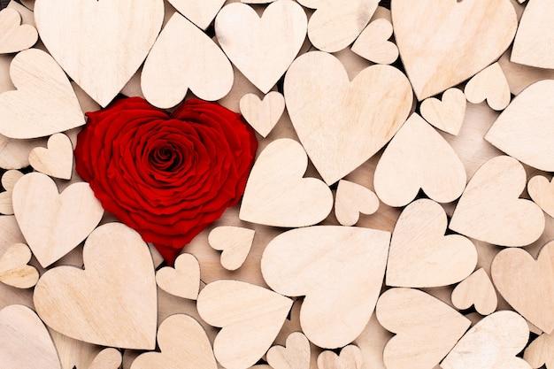 Holzherzen, ein rotes herz stieg auf dem hölzernen herzhintergrund auf. holzherz und rosenblume
