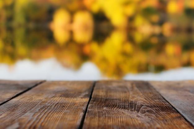 Holzhintergrund auf dem hintergrund des herbstwaldes und des sees oder des flusses in der unschärfe.